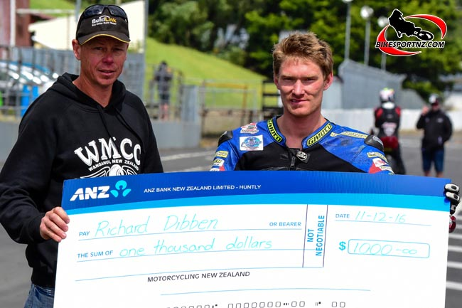 Whanganui's Richie Dibben receives a cheque from MNZ, handed to him by Wanganui Motorcycle Club president Colin Matthews (left) at Manfeild on Sunday. Photo by Andy McGechan, BikesportNZ.com